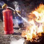 MR S+  A man using a water-based fire extinguisher to put out a fire.
